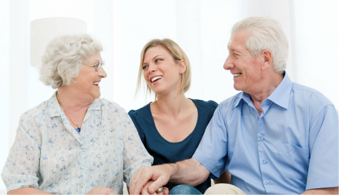 happy senior couple with a caregiver